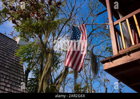 The American Flag flies high from a balcony with a tree with hanging Spanish moss, blue skies and a house with cedar shingles in the background.