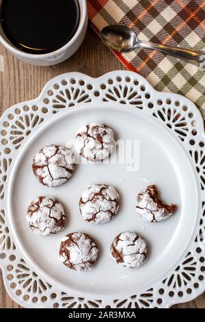 Table top setting with Chocolate Almond Crinkle cookies on a white plate with coffee for the holiday season - Stock Photo
