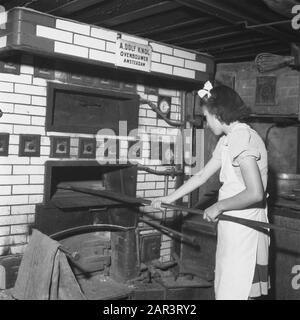Children's broadcast to England  She goes to England (3). She puts the loaves in the big oven and remembers that a few months ago there was no work in the bakery because there was no wheat flour. Now the liberators have brought flower and they will take her to their country to be able to repair there Annotation: On the oven a sign with the text A. Dolf Tuber Ovenbuilder Amsterdam Date: September 1945 - Stock Photo