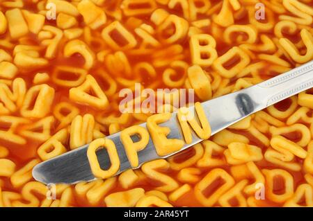 Alphabet spaghetti spelling open with random letters in tomato sauce background - Stock Photo