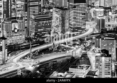 Densely populated and developed Greater Osaka city at sunset with bright illumination of skyscraper towers - black-white impression. - Stock Photo