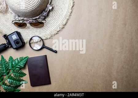 Top view of accessories used for leisure travelers on a brown background. Travel accessories and copy space. Concept of top view travel accessories.