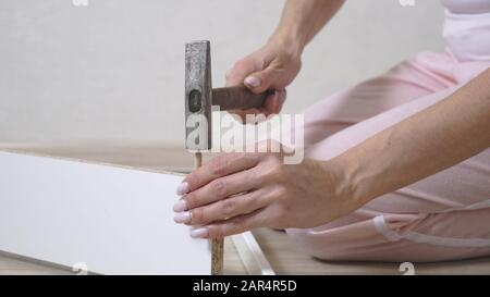 woman collects white furniture at home using a hammer. Close-up. - Stock Photo