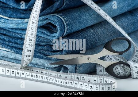 Blue cotton jeans folded on a table with a tape measure and scissors on a white isolated background.