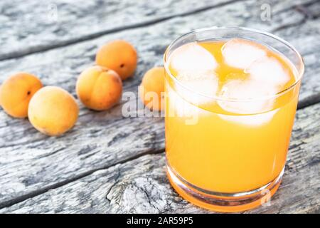 Fresh apricot juice with apricots and ice cubes in a glass against the background of old boards. Summer soft drinks. Close-up. - Stock Photo