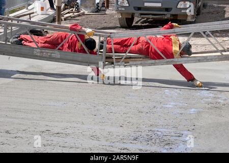 Two construction workers leveling freshly poured concrete mix - Stock Photo