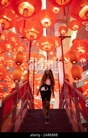 Happy admiring woman enjoying traditional red lanterns decorated for Chinese new year Chunjie. Cultural asian festival in Hong Kong. - Stock Photo