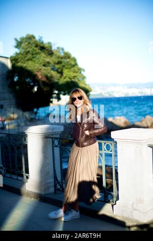 Full length shot of happy mature woman wearing biker jacket and sunglasses while standing by the sea.