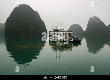 Tourist Azalea cruise ship anchored in misty weather with limestone karst rock formations reflected in the sea, Halong Bay, Vietnam, Asia - Stock Photo