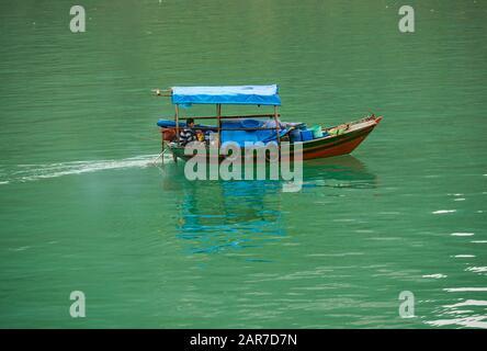 Asian man in traditional Vietnamese fishing boat, Halong Bay, Vietnam, Asia - Stock Photo