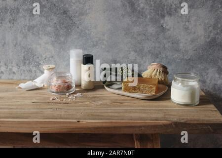 Still life of organic handmade soap bar, wooden brush, moisturizer, shampoo, Himalyan salt and eucalyptus on wooden table. Spa, herbal skin cosmetics - Stock Photo
