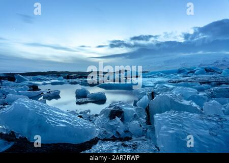 iceland glacier jokulsarlon in the evening icebergs floating on the cold peaceful water after sunset with dramatic sky . - Stock Photo