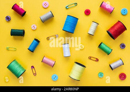 Flat lay with spools of colored thread, buttons and safety pins on yellow background - Stock Photo