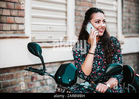 Happy cheerful young woman talking on the phone in the street, smiling girl making answering call by cellphone sitting on her scooter. Beautiful lady - Stock Photo
