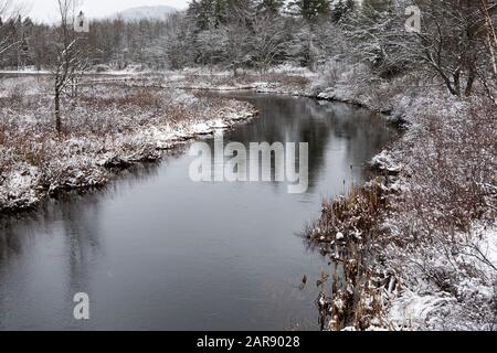 A snowy winter scene of the Sacandaga River near Speculator, NY USA in the Adirondack Mountains. - Stock Photo