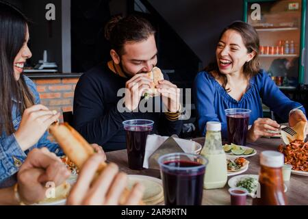 Mexican people eating Tacos al Pastor in a Taqueria in Mexico city - Stock Photo