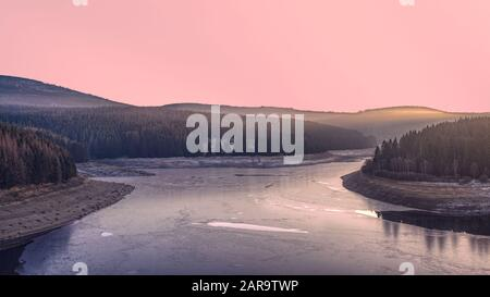Frozen dam in the winter forest at sunset. A pink illuminated sky above Ecker Reservoir and Ecker Dam near Bad Harzburg, Harz mountain range, Germany. - Stock Photo