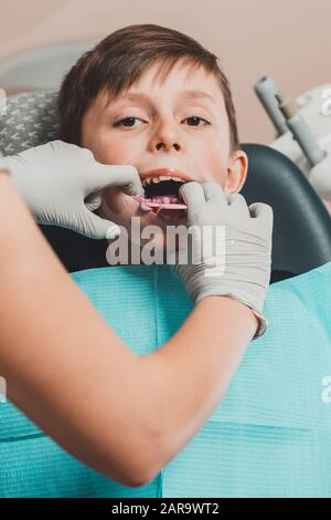 Boy in dentist chair with dental impression tray in her mouth - Stock Photo