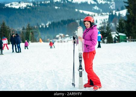 Woman stands on top of mountain in ski outfit, on sky and mountains background. - Stock Photo