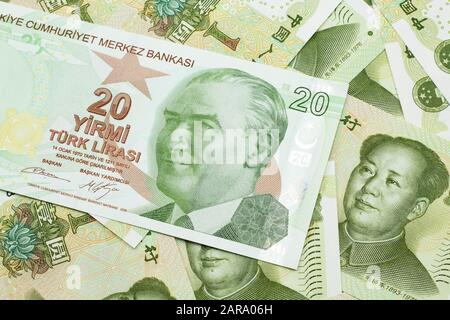 A close up image of a green twenty Turkish lira bank note on a background of Chinese one yuan bank notes in macro - Stock Photo
