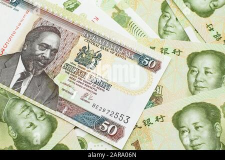 A close up image of a fifty Kenyan shilling bank note in macro with Chinese one yuan bills - Stock Photo