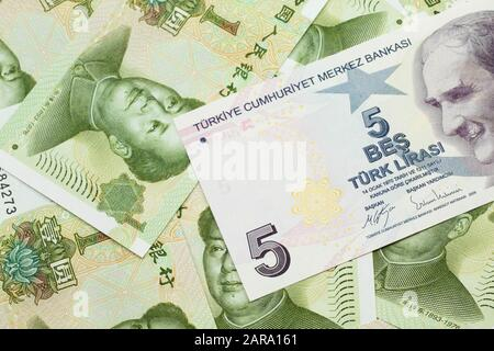 A close up image of a purple five Turkish lira bank note on a background of Chinese one yuan bank notes in macro - Stock Photo