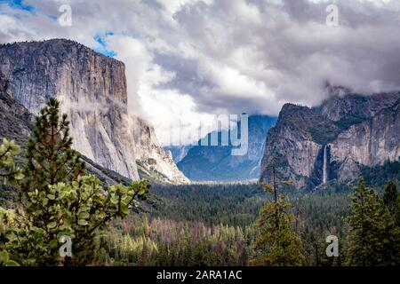 Classic view of Yosemite Valley featuring famous El Capitan, Cathedral Rocks, Bridalveil Fall and Half Dome and Cloud Rest hidden behind the clouds. - Stock Photo