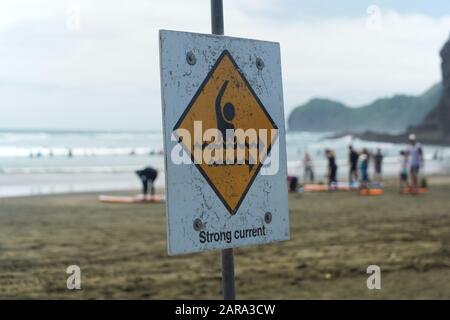 Piha South Beach, Auckland West Coast New Zealand. Summer day.  strong current white and yellow lifeguard warning sign People taking surfing lesson - Stock Photo