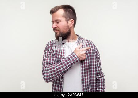 Get out! Portrait of angry bearded man in casual plaid shirt pointing finger to the side and turned away, looking irritated disappointed with your beh - Stock Photo