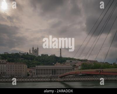 A crossing bridge over the river Saône in the foreground leading towards the Basilique de Fourviere on top of the hill in Lyon - Stock Photo