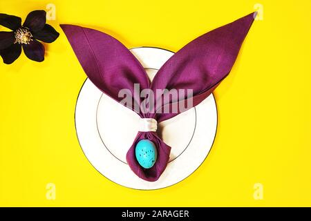Beautiful Easter table setting with egg, purple napkin Easter Bunny on white plate and flower on yellow background. Flat lay, top view. - Stock Photo