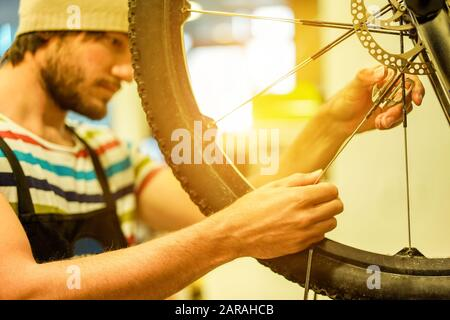 Stylish bearded bicycle mechanic doing his professional work in workshop - Young trendy man checking spoke wheel - Repairing bikes concept -  Focus on
