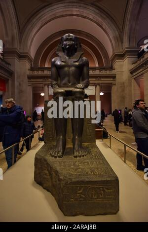 Colossal Seated Statue of a Pharaoh in the Great Hall of the Metropolitan Museum of Art of New York City , 'the Met', the largest art museum of USA. - Stock Photo