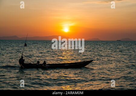 Two fishing boats silhouetted against the setting sun in the Gulf of Thailand off Kep, Cambodia, SE Asia - Stock Photo