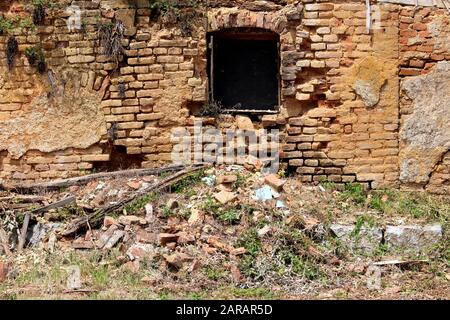 Broken window mounted on red brick wall of ruins of destroyed old wooden and bricks suburban family house mixed with small plants in old part of town - Stock Photo