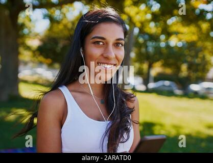 Portrait of a smiling young woman with earphones in her ears looking at camera in the park - Happy young woman listening to music at outdoors - Stock Photo