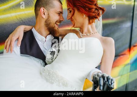 Groom holding bride on his hands in front of graffiti wall - Stock Photo