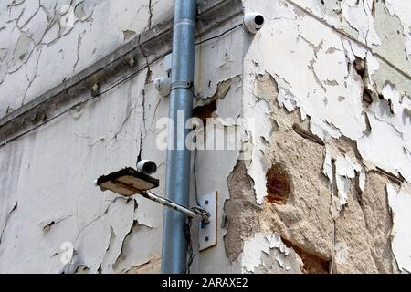 Three new closed circuit TV CCTV security cameras mounted on corner of old abandoned building with dilapidated cracked facade next to new gutter pipe - Stock Photo