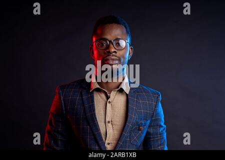 Closeup portrait of young handsome confident serious bearded african businessman in glasses, wearing shirt, checked suit, looking at camera, standing - Stock Photo