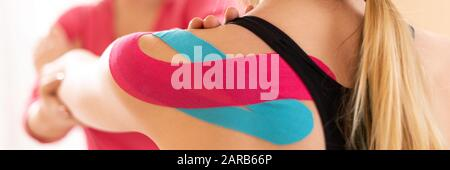 Kinesiology, physical therapy, rehabilitation banner. Female patient wearing kinesio tape on her shoulder exercising with a professional physical ther - Stock Photo