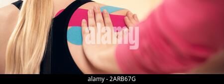 Physical therapist applying kinesio tape on female patient's shoulder. Close up rear view banner. Kinesiology, physical therapy, rehabilitation concep - Stock Photo