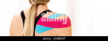 Rear view of a female patiet with kinesio tape on her shoulder. Kinesiology, physical therapy, rehabilitation banner. - Stock Photo