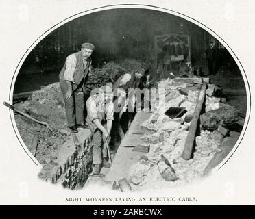 Workmen working in the streets at night laying electrical cable.     Date: 1900 - Stock Photo