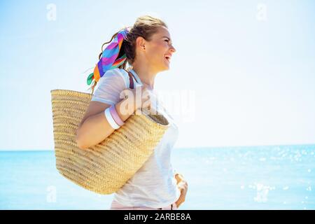 happy young woman in white t-shirt with beach straw bag looking into the distance on the ocean shore. - Stock Photo