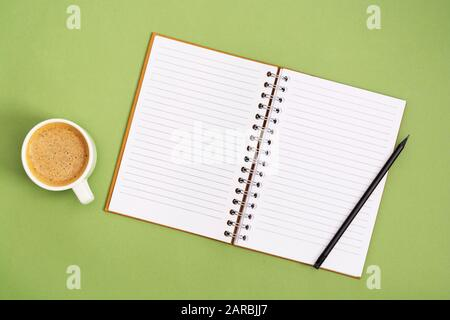 Open notebook with empty page and coffee cup. Table top, work space on green background. Creative flat lay. - Stock Photo