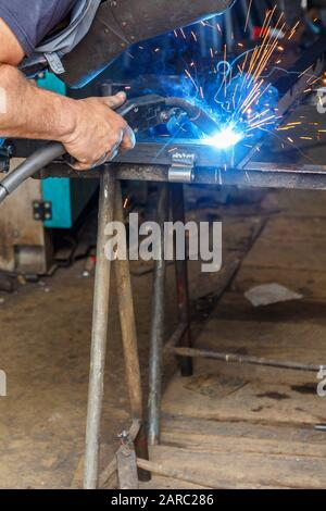 Man welding in a workshop - Stock Photo