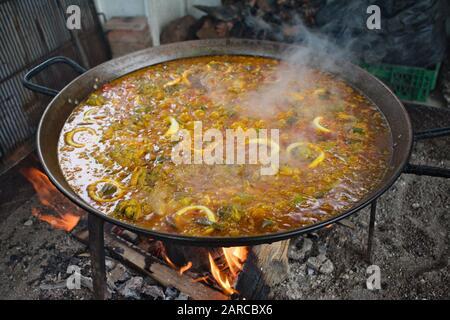 Big metal pan cooking Paella  on open flames - Stock Photo