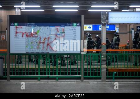 Hong Kong - Jan 21, 2020:  Peaceful sit down at Yuen Long MTR station. Protestors sticking up sign. - Stock Photo