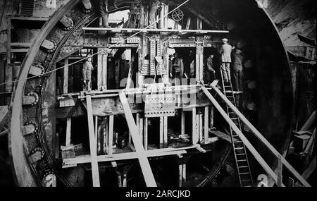 20th century workers in cylindrical tunnelling shield, protective structure used during the excavation of large, man-made tunnels - Stock Photo