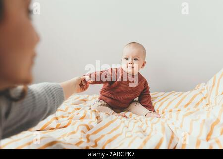 Beautiful little baby girl on the bed in a cozy brown sweater smiles. Concept of motherhood and childhood. Adorable six month old baby girl lying on the bad and looking into the camera. Mother hold little hand.
